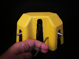 Image of a counter-mounted Burner Brake covering a gas jet fixture; this Burner Brake is equipped with a removable fastener that is being inserted.